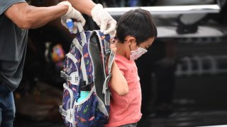 In this Sept. 10, 2020, file photo, a staff member helps a student put on his knapsack as he arrives at STAR Eco Station Tutoring & Enrichment Center where he will follow his remote school classes in Culver City, California.