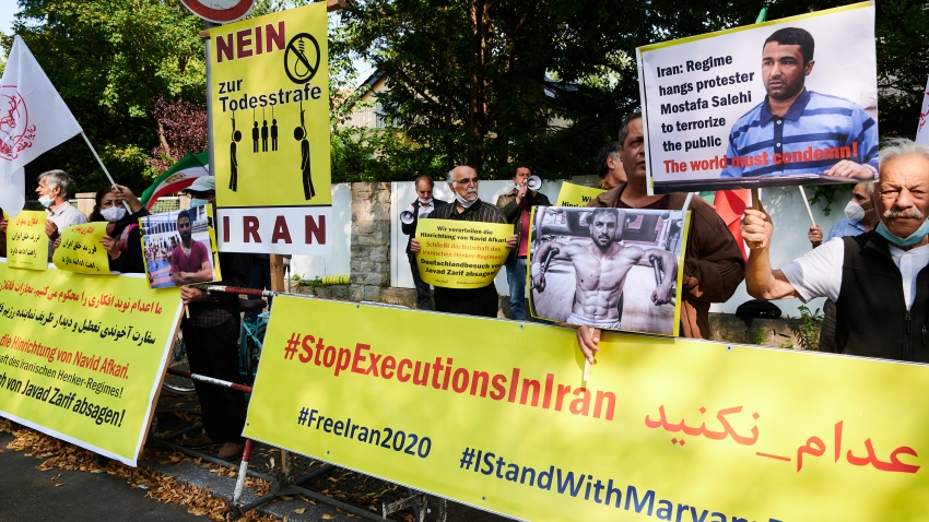 In this Sept. 12, 2020, photo, demonstrators are holding banners in front of the Iranian Embassy in Berlin to protest against the execution of the wrestler Navid Afkari