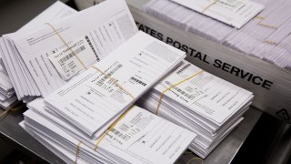Sample voting ballots sit in a pile