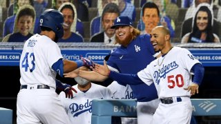 Edwin Rios #43 of the Los Angeles Dodgers celebrates with teammates Justin Turner and Mookie Betts .