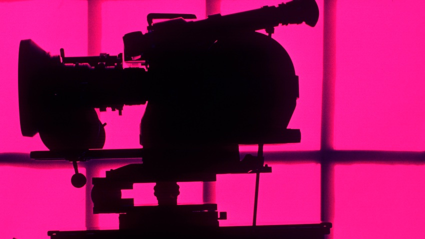 Silhouetted motion picture camera.