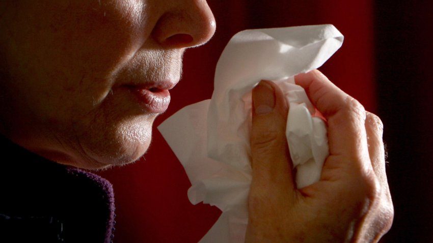 A close-up view of a woman blowing her nose.