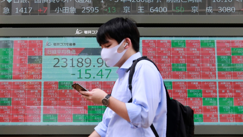 A man walks by an electronic stock board of a securities firm in Tokyo, Monday, Sept. 7, 2020. Asian stock markets were mixed Monday after Wall Street turned in its biggest weekly decline in more than two months.