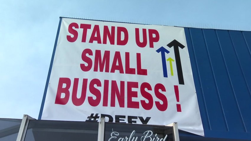 "A sign that reads, ""Stand Up Small Business #Defy"" rests above Rudford's Restaurant."