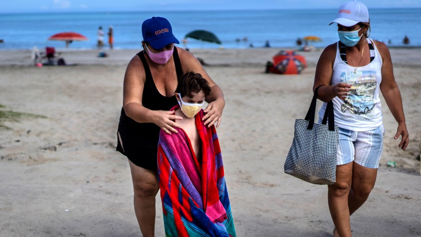 Wearing a mask as a precaution against the spread of the new coronavirus, a woman towels off a child at a beach in Havana, Cuba, Sunday, Oct. 11, 2020.