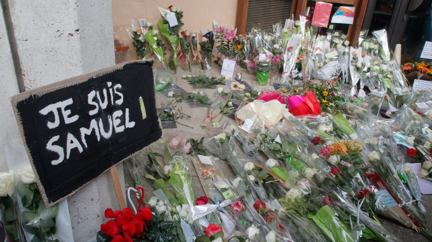 "A poster reading ""I am Samuel"" and flowers lay outside the school where slain history teacher Samuel Paty was working, Saturday, Oct. 17, 2020 in Conflans-Sainte-Honorine, northwest of Paris"