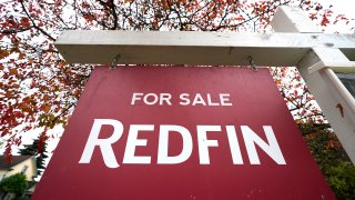 """A Redfin """"for sale"""" sign stands in front of a house"""