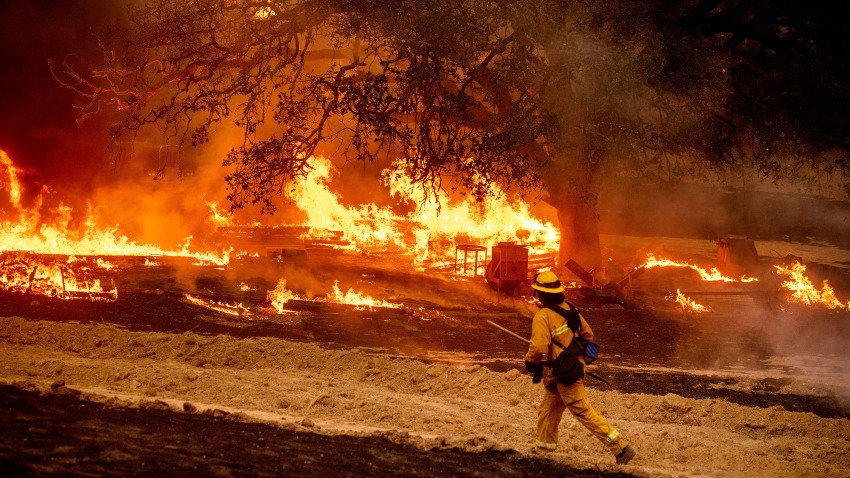 A firefighter passes flames while battling the Glass Fire in a Calistoga, Calif., vineyard Thursday, Oct. 1, 2020.