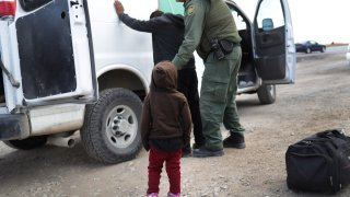 A child watches as a U.S. Border Patrol agent searches a Central American immigrant