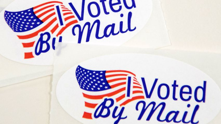 "In this Sept. 4, 2020, file photo, stickers that read ""I Voted By Mail"" sit on a table waiting to be stuffed into envelopes by absentee ballot election workers at the Mecklenburg County Board of Elections office in Charlotte, North Carolina."