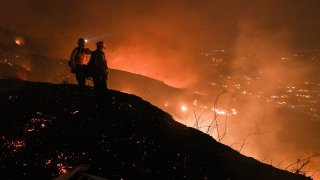 Firefighters look out over a burning hillside as they fight the Blue Ridge Fire in Yorba Linda, California.