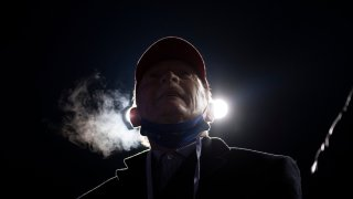 A man watches as President Donald Trump speaks during a Make America Great Again rally