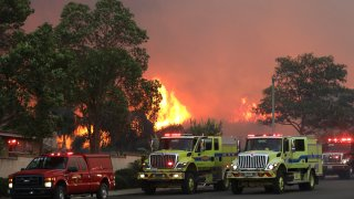 Firetrucks stage on Elinvar Drive in Chino Hills as the Blue Ridge Fire burns in Chino Hills State Park near homes.