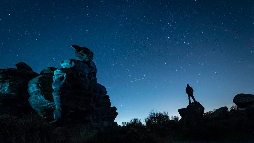 An airplane flies in the night sky above a stargazer amid the Orionid meteor shower at Brimham Rocks in Yorkshire, England, Oct. 22, 2018.