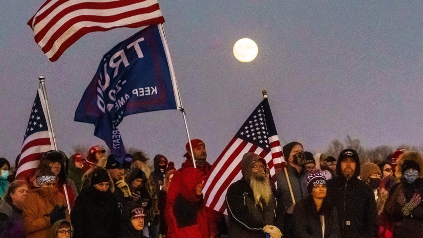"""Supporters of U.S. President Donald Trump listen during a """"Make America Great Again"""" rally at the Rochester International Airport in Rochester, Minnesota, Oct. 30, 2020."""