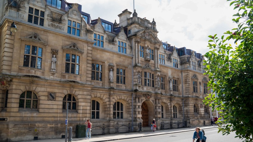 Pedestrians and a cyclist pass Oriel College, where a statue of Cecil Rhodes stands above an entrance, at the University of Oxford in Oxford, U.K., on Monday, July 20, 2020.