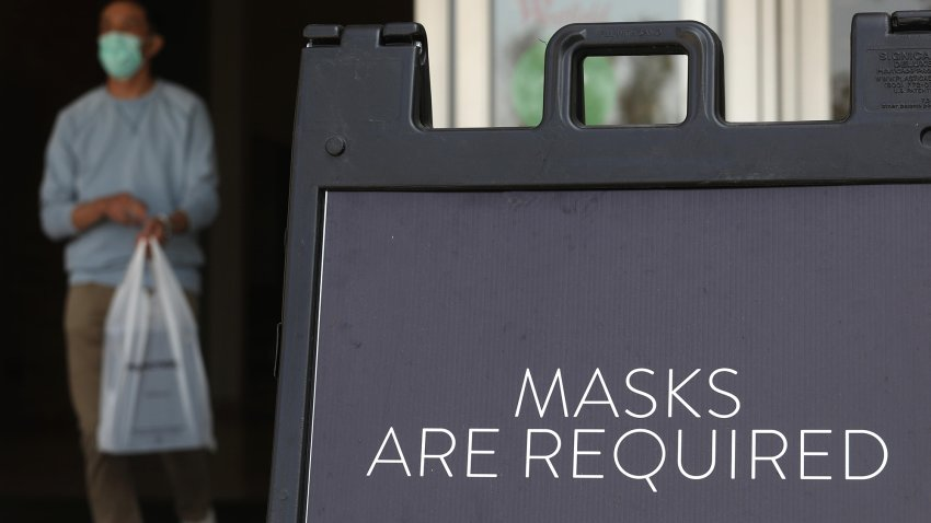 A sign tells customers to wear masks to prevent the spread of COVID-19.