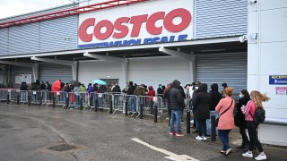 Shoppers wait outside a Costco wholesale store in Leeds, northern England