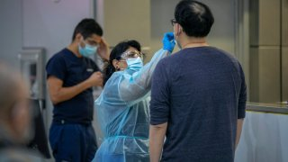 In this Nov. 25, 2020, file photo, a traveler is tested COVID-19 at LAX Tom Bradley International Terminal on Thanksgiving eve as the coronavirus spike worsens and stay-at-home restrictions are increased in Los Angeles, California.
