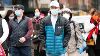 In this Nov. 15, 2020, file photo, people wear face masks in Chinatown as the city continues the re-opening efforts following restrictions imposed to slow the spread of coronavirus in New York City.