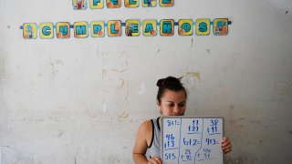 Gabriela Fajardo, a 26-year-old Honduran seeking asylum in the United States, teaches a Zoom class for Central American children living in camps, various shelters and apartments in other parts of Mexico, Nov. 20, 2020, from a hallway of a building in Matamoros, Mexico.