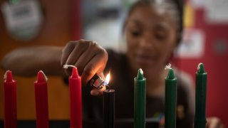 Kamora Shambley lite the first of seven candles during a celebration of the first day of Kwanzaa at the Martin Luther King Recreation Center Wednesday December 26, 2018 in St. Paul, MN.]   Jerry Holt • Jerry.holt@startribune.com