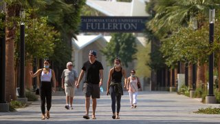 New incoming student Olivia Murphy, 20, left in white top, takes her family on a tour of the campus at Cal State University of Fullerton on Friday, Aug. 21, 2020 in Fullerton, CA.
