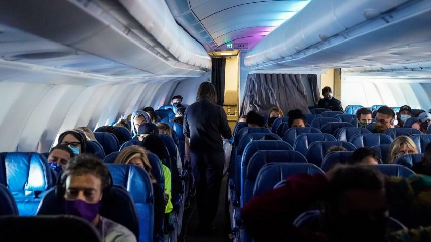 美国夏威夷州檀香山--10月15日:戴着面具的乘客,在2020年10月15日星期四从洛杉矶国际机场飞往檀香山国际机场的夏威夷航空公司航班上,在太平洋上空。在持续的冠状病毒大流行中,夏威夷州正试图重启其旅游经济;10月15日是一个新的旅行者测试计划的开始,预计将有数千人抵达该州。(Kent Nishimura / Los Angeles Times via Getty Images)(photo:NBCLA)