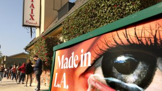 People wait in line for a free COVID19 test in front of a closed Taix French Restaurant in Echo Park.