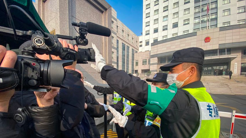 A policeman covers a camera to stop journalists from recording footage outside the Shanghai Pudong New District People's Court, where Chinese citizen journalist Zhang Zhan - who reported on Wuhan's COVID-19 outbreak and placed under detention since May - is set for trial in Shanghai on December 28, 2020.