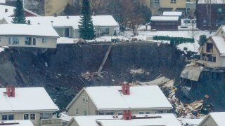 Destroyed houses are seen in a crater left behind by a landslide in Norway