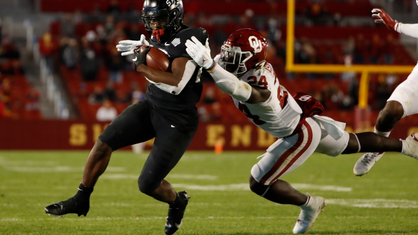AMES, IA - OCTOBER 3: Running back Breece Hall #28 of the Iowa State Cyclones rushes for yards as linebacker linebacker Brian Asamoah #24 of the Oklahoma Sooners puts pressure on in the first half of the play at Jack Trice Stadium on October 3, 2020 in Ames, Iowa. The Iowa State Cyclones won 37-30 over the Oklahoma Sooners. (Photo by David K Purdy/Getty Images)