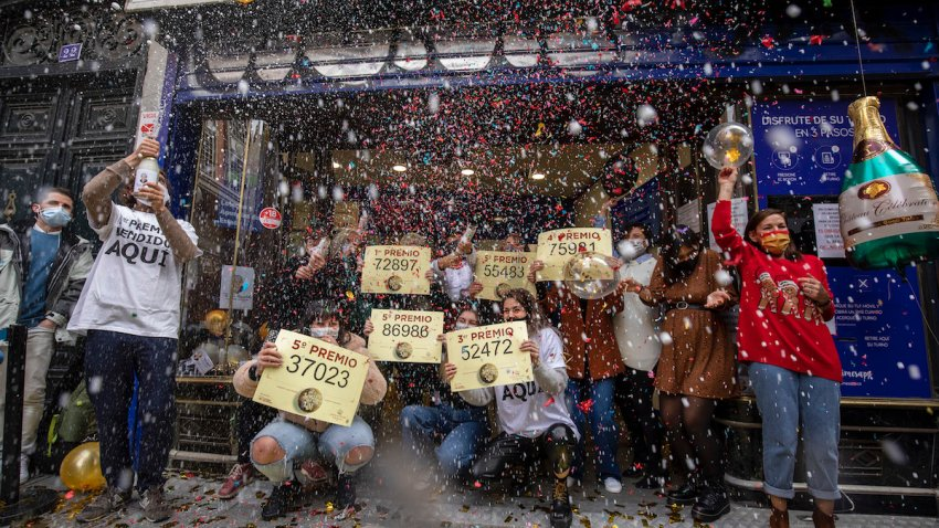 'Doña Manolita' lottery shop owners and employees celebrate after selling the winning ticket number of Spain's Christmas lottery named 'El Gordo' (The Fat One)