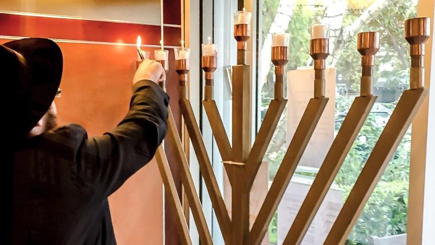 在加利福尼亚州圣莫尼卡的一个辅助生活空间,一名Chabad志愿者为光明节第六夜的开始点燃了烛台蜡烛。(photo:NBCLA)