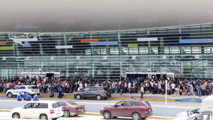 Travelers stand in line outside of Luis Muoz Marn International Airport after Hurricane Maria disrupted flight service in San Juan, Puerto Rico on Wednesday, Sept. 27, 2017. President Donald Trump said he may temporarily suspend a law that restricts the use of foreign ships operating in U.S. waters and between U.S. ports in order to accelerate the delivery of aid to Puerto Rico, where his administration faces mounting criticism over its response to Hurricane Maria.