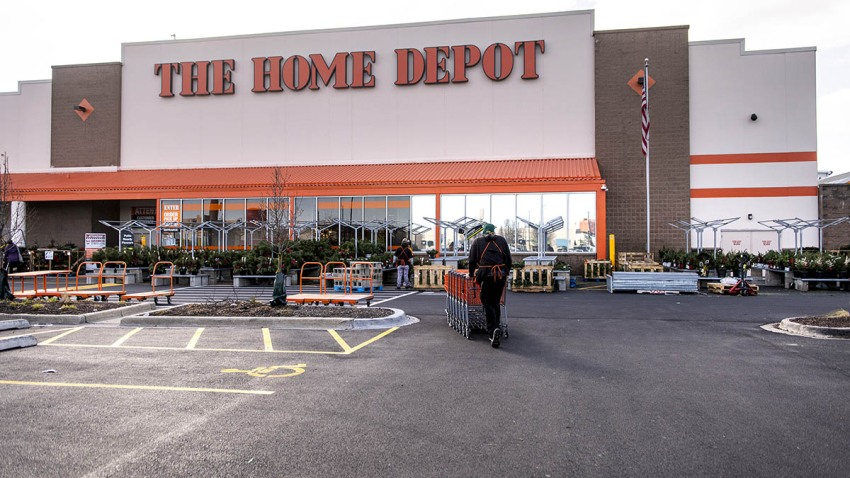 An employee gathers shopping carts from the parking lot of a Home Depot Inc. store in Chicago, Illinois, U.S., on Monday, Nov. 23, 2020.