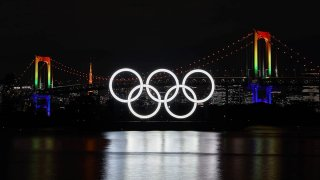 In this Dec. 1, 2020, file photo, the illuminated Olympic rings, Rainbow Bridge and Tokyo Tower are seen at Tokyo Bay area, in Tokyo, Japan.