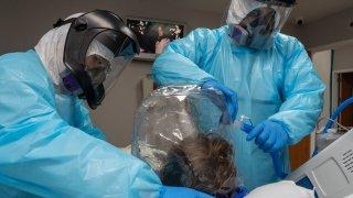 Personal médico en Texas usan un casco con ventilador en un paciente de cuidados intensivos en Houston.