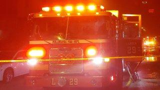 A Philadelphia Fire Department truck has its lights on as it parks behind crime scene tape following a fatal blaze in the West Oak Lane neighborhood.