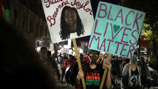 """In this Nov. 7, 2020, file photo, a person holds a sign reading """"Black Lives Matter"""" during a rally at Nubian Square in Roxbury"""