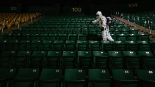 Alexander Espinoza of V&G Cleaning Services uses an electromagnetic sanitizer with hospital-grade disinfectant to sterilize theGeorge Mason Patriots men's basketball spectator seating bowl against the novel coronavirus after their men's NCAA basketball game against the La Salle Explorers at Eagle Bank Arena on January 13, 2021 in Fairfax, Virginia.