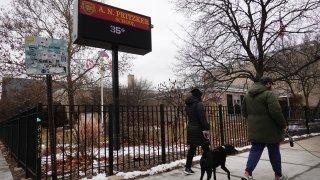 Residents walk dogs outside of Pritzker Elementary School