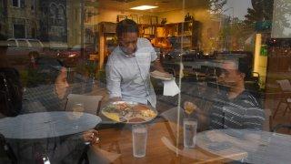 Michael Demissie, C, serves Tevi'a Johnson, L, and Tivon Johnson at Zenebech Restaurant in Washington, DC.