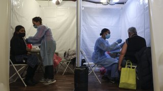 Healthcare workers administer Pfizer-BioNTech COVID-19 vaccines at a vaccination site inside a church in the Bronx borough of New York, on Friday, Feb. 5, 2021.
