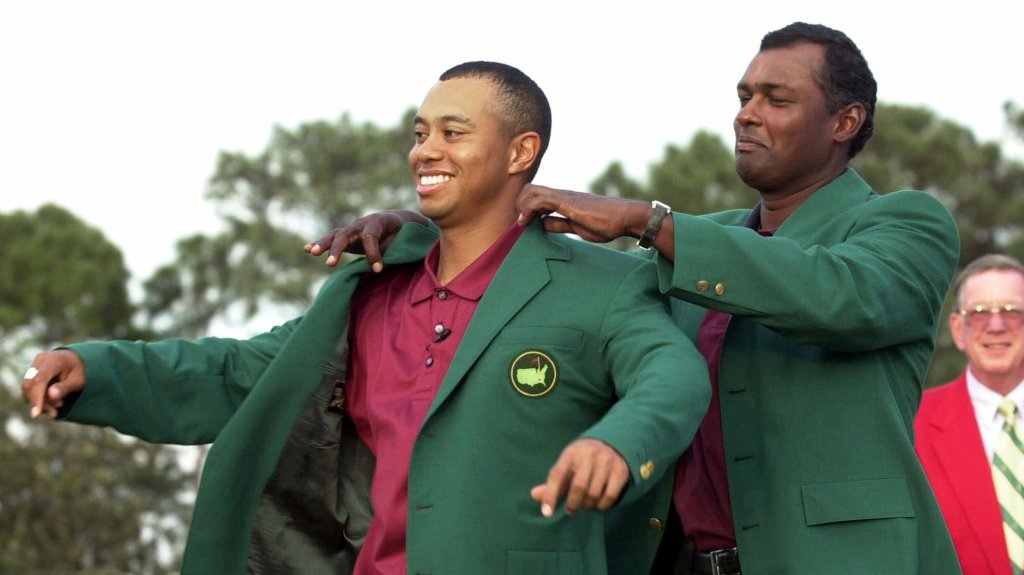 Tiger Woods, left, receives his Masters green jacket from last year's champion Vijay Singh of Fiji, after winning the 2001 Masters at the Augusta National Golf Club in Augusta, Ga., Sunday, April 8, 2001.