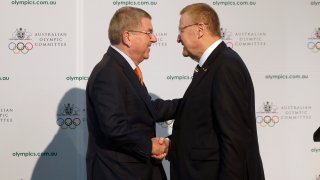 """FILE - In this Saturday, May 4, 2019 file photo, International Olympic Committee President Thomas Bach, left, shakes hands with Australian Olympic Committee (AOC) President John Coates at the AOC annual general meeting in Sydney, Australia. The Australian Olympic bid is on a fast-track to host the 2032 Olympics Wednesday Feb. 24, 2021, after the International Olympic Committee executive board gave Queensland """"preferred bidder"""" status, 11 years ahead of the games."""