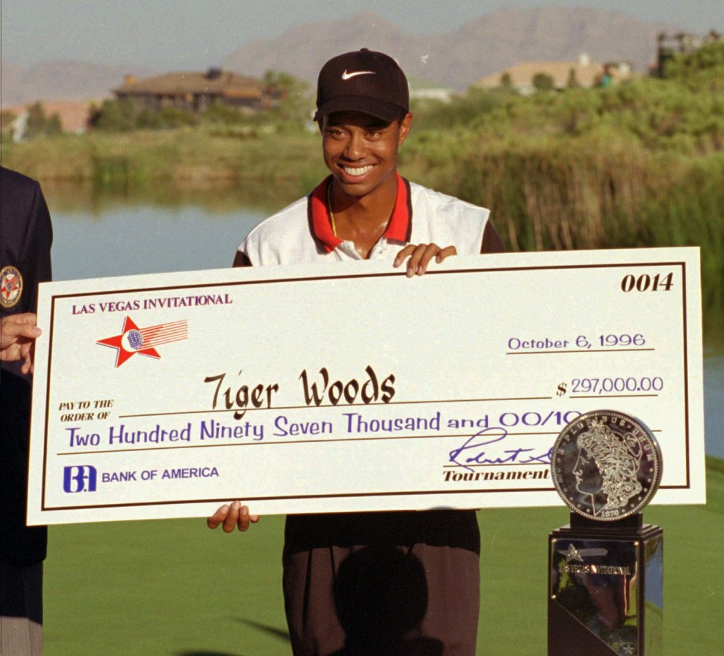 Rookie pro golfer Tiger Woods smiles after receiving a check and trophy for winning the Las Vegas Invitational Sunday, Oct. 6, 1996, at the TPC at Summerlin in Las Vegas.