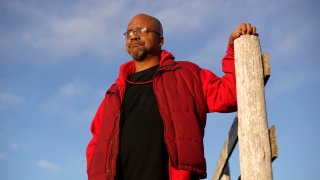 """Lateef Dowdell stands on land once belonging to his uncle Gil Alexander, who was the last active Black farmer in the community of Nicodemus, Kan., Thursday, Jan. 14, 2021. Dowdell moved back to Nicodemus, a settlement founded by former slaves known as """"exodusters"""" in the 1870s, several years earlier to take over the farm after his uncle died, but soon after lost most of the land when the bank foreclosed. New legislation in Congress aims to remedy historical inequities in government farm programs that have helped reduce the number of Black farmers in the United States from about a million in 1920 to less than 50,000 today."""