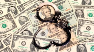handcuffs sitting on top of a pile of us dollars of assorted denominations