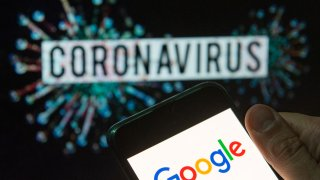 In this photo illustration the American multinational technology company and search engine Google logo seen displayed on a smartphone with a computer model of the COVID-19 coronavirus on the background.